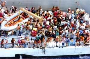 "FILE-In this Aug. 24, 1994 file photo, more than one hundred Cuban refugees await to disembark onto a U.S. Naval warship from the Coast Guard Cutter Baronof about 50 miles south of the coast of Key West, Fla. In the 20 years since Fidel Castro set off a high-seas humanitarian crisis by encouraging an exodus of 35,000 islanders, more than 26,000 other Cubans have risked their lives crossing the Florida Straits. Already this year, nearly 3,000 have been picked up by U.S. authorities, on a pace to double last year's total. Experts say it shows the limits of the ""wet-foot, dry-foot"" policy that solved the 1994 crisis. (AP Photo/Hans Deryk, File)"