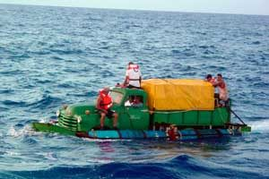 Twelve Cuban migrants attempt to cross the Straits of Florida Wednesday, July 16, 2003, in a boat fashioned out of a 1951 Chevy pickup truck driving it within 40 miles of the United States before they were found by the U.S. Coast Guard and returned to the island. (AP Photo/U.S. Coast Guard, Gregory Wald)