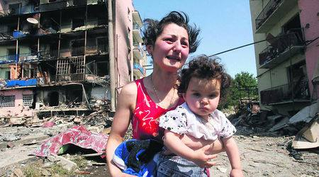Грузинска майка с детето си, оцеляла по чедо след бомбардировката на руските варвари, плаче пред разрушения си дом